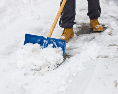 Shoveling snow off of a sidewalk